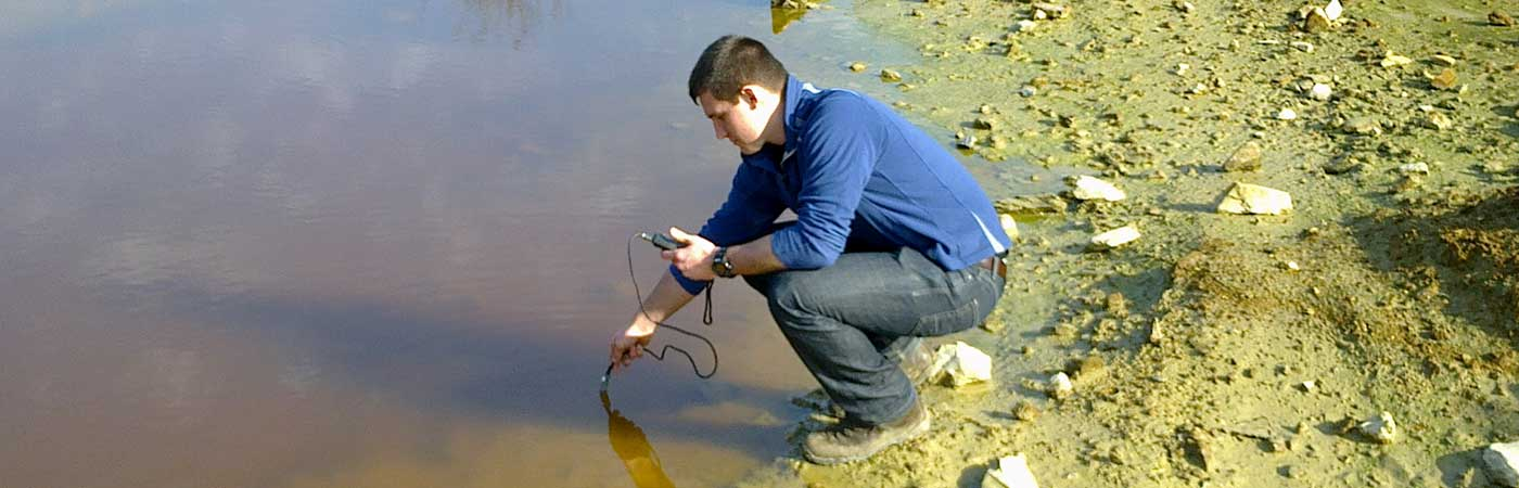 'Student measuring the water pH in abandoned mile tailings at Wheal Maid in Cornwall.