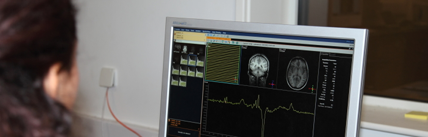 A member of psychology research staff reviewing brain scan images at Bangor University