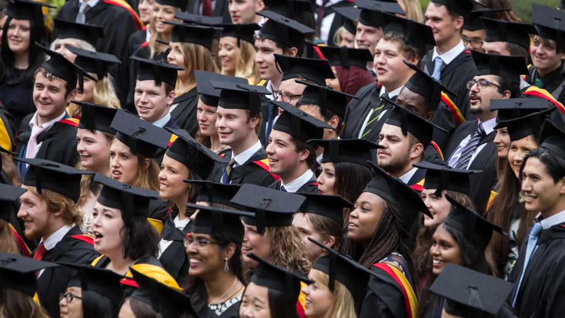 Students in their cap and gowns celebrating after their graduation ceremony
