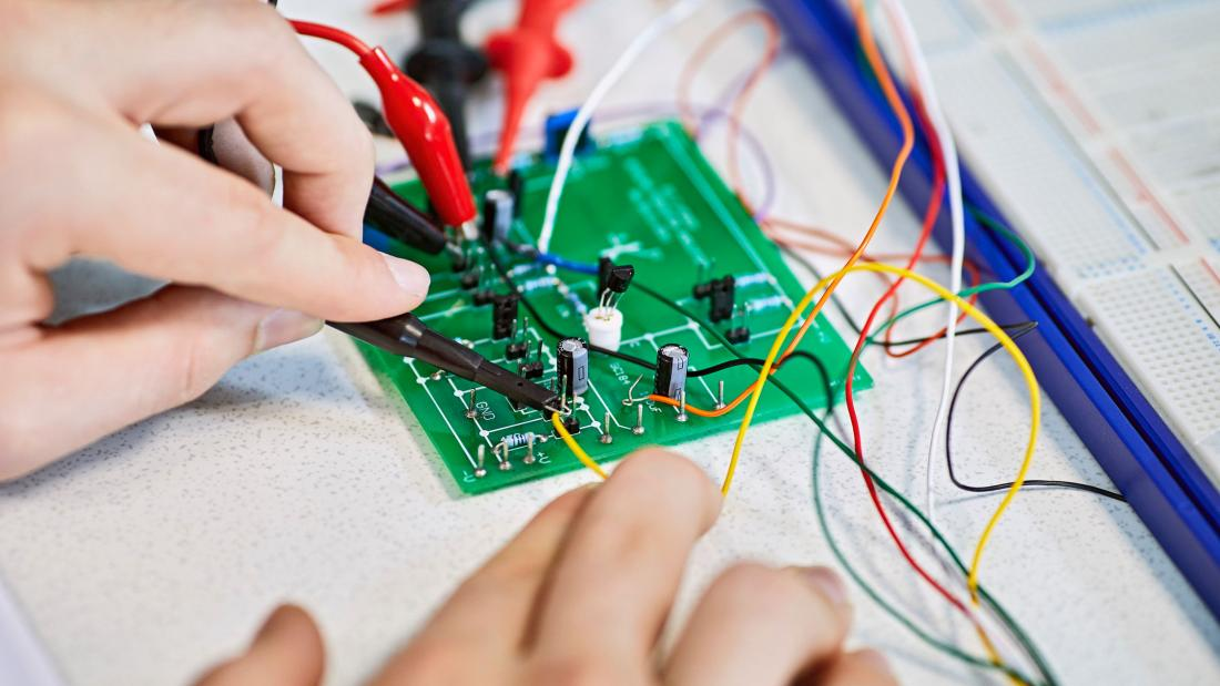 A student using a circuit board and crocodile clips in a computer science and electronic engineering lab