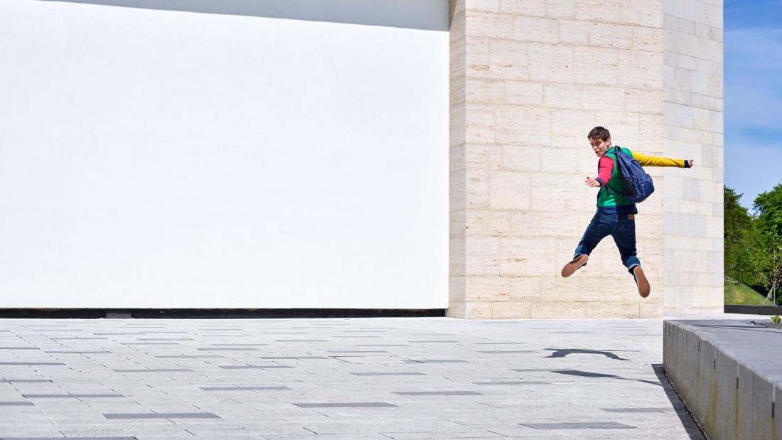 A student jumping outside the Pontio building