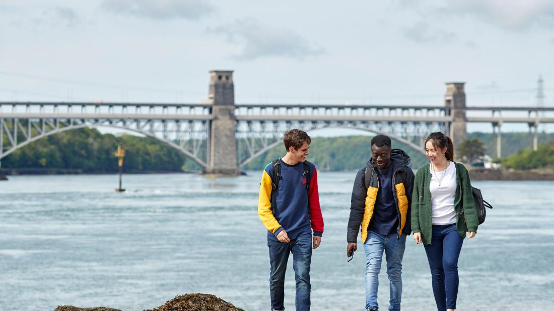 Three students walking along the beach with the Britannia bridge in the background