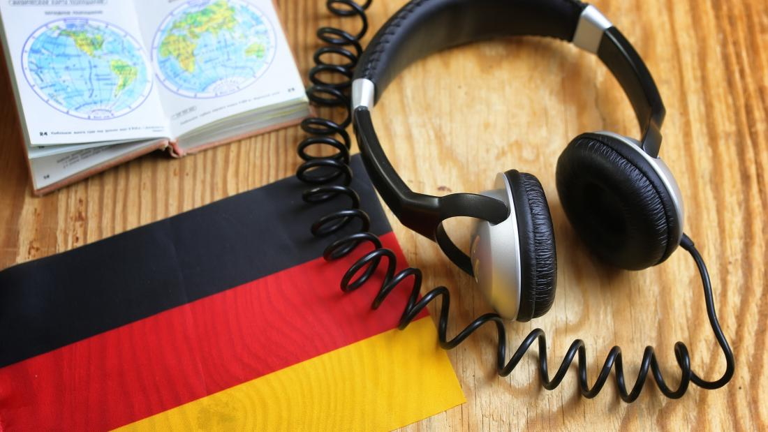 Headphones and book on a desk with a German flag