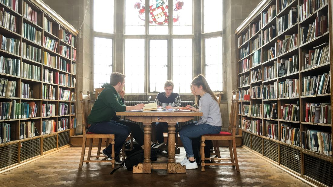 Students reading and working together in one of the libraries traditional reading rooms, on the Main Arts campus