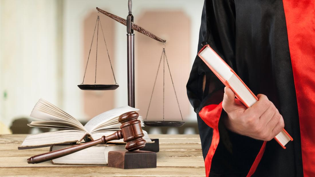 Image of Law student in robe with scales in background