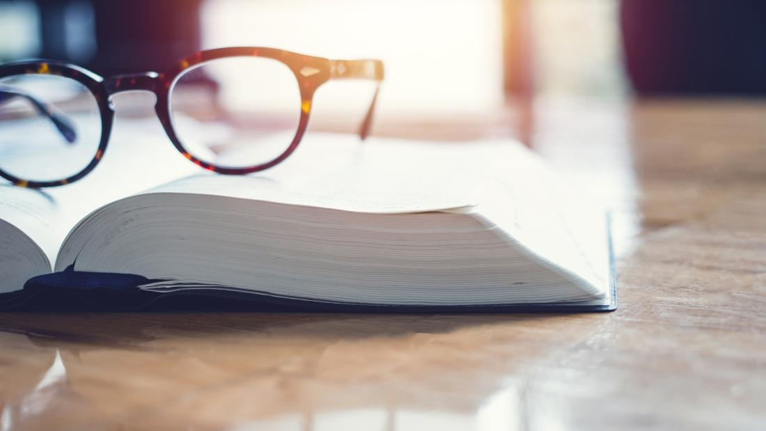 A pair of glasses resting on an open book