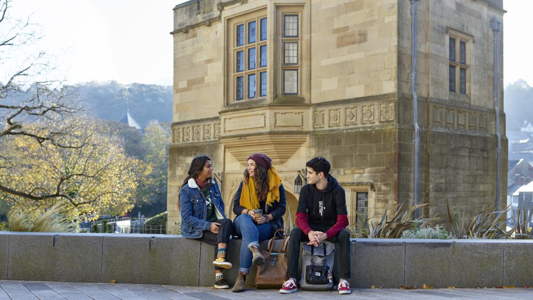 Students sitting in front of Bangor University's Memorial Arch