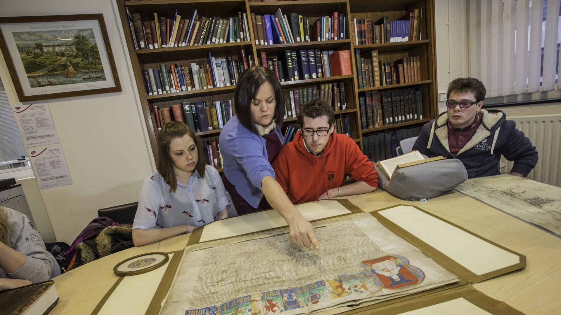 Seminar setting with tutor and students looking at a historic document.