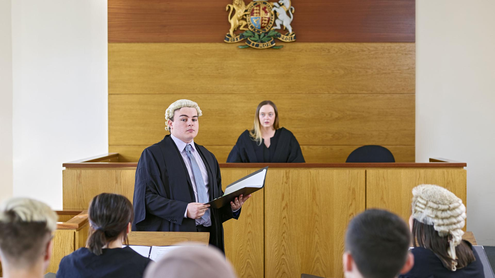 Students wearing robes and wigs in a moot court
