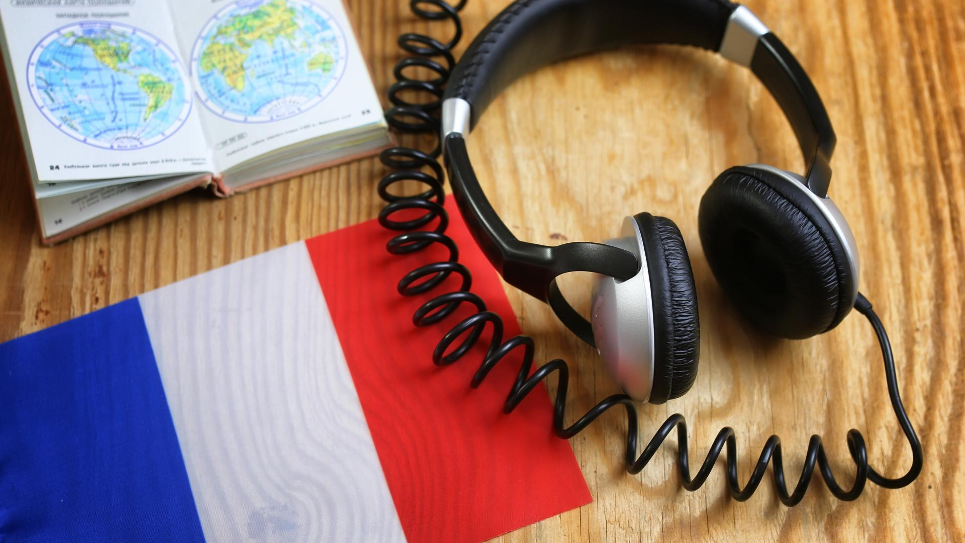 Headphones and book on a desk with a French flag