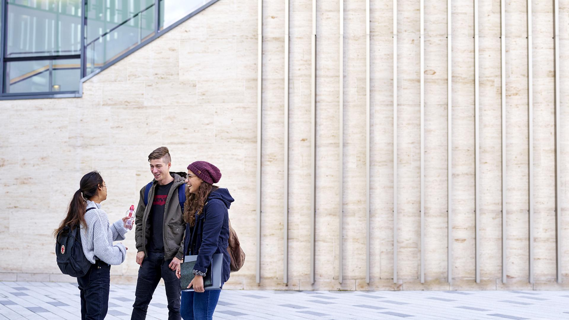 Three students chatting outside the Pontio building