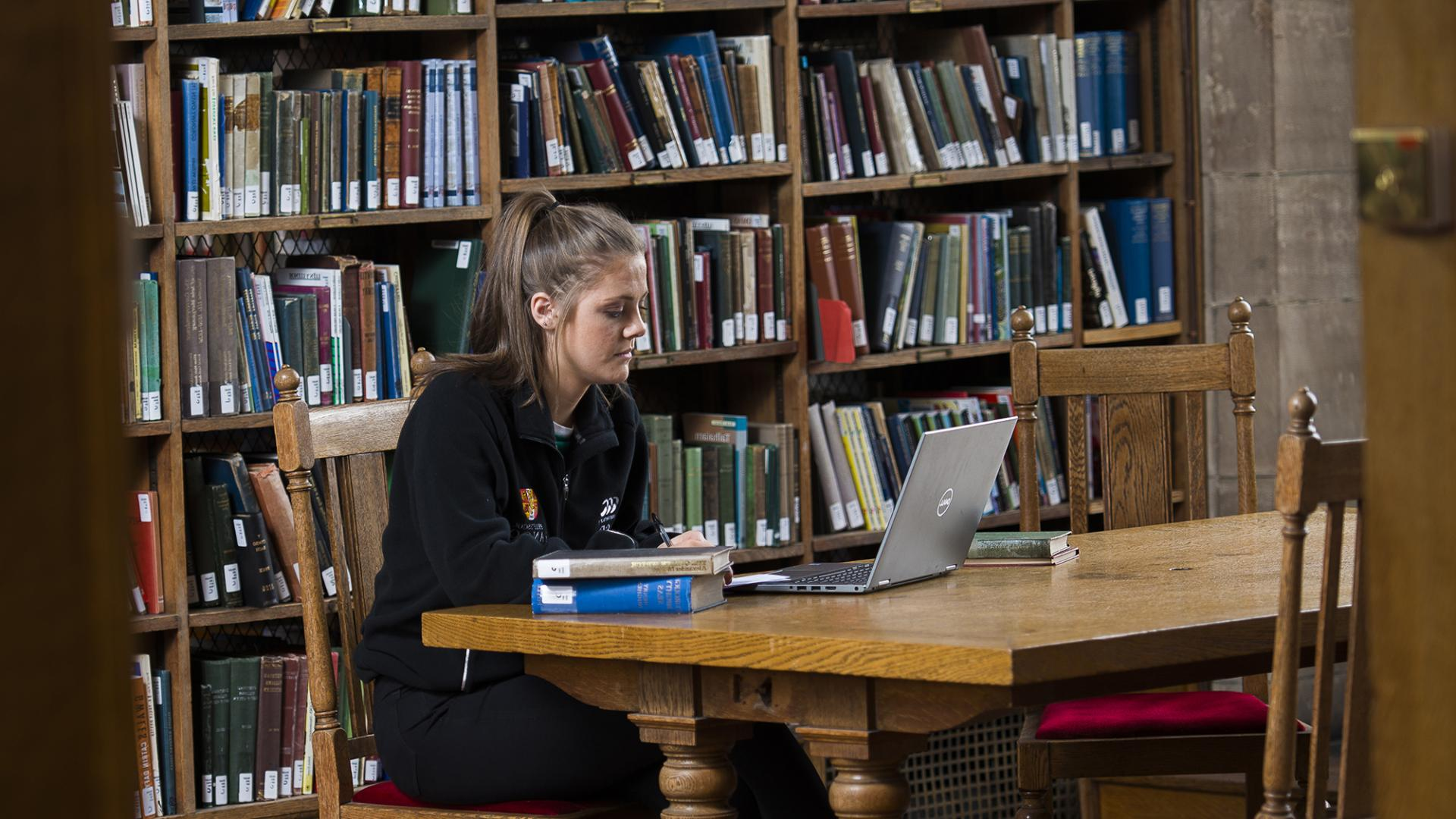 A student at work in the Library, books and laptop on the table