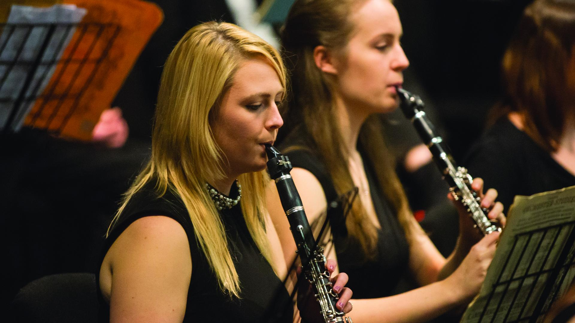 Two students playing clarinet in an orchestra