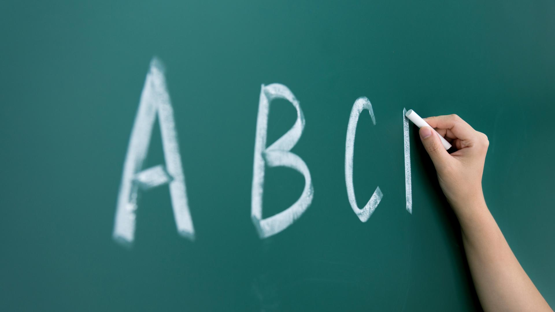 Writing A,B,C's on classroom blackboard