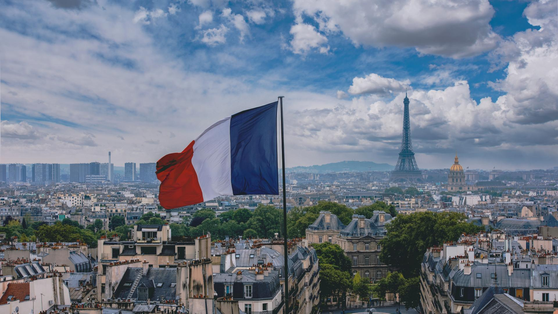French flag flying in Paris with Eiffel Tower in the background