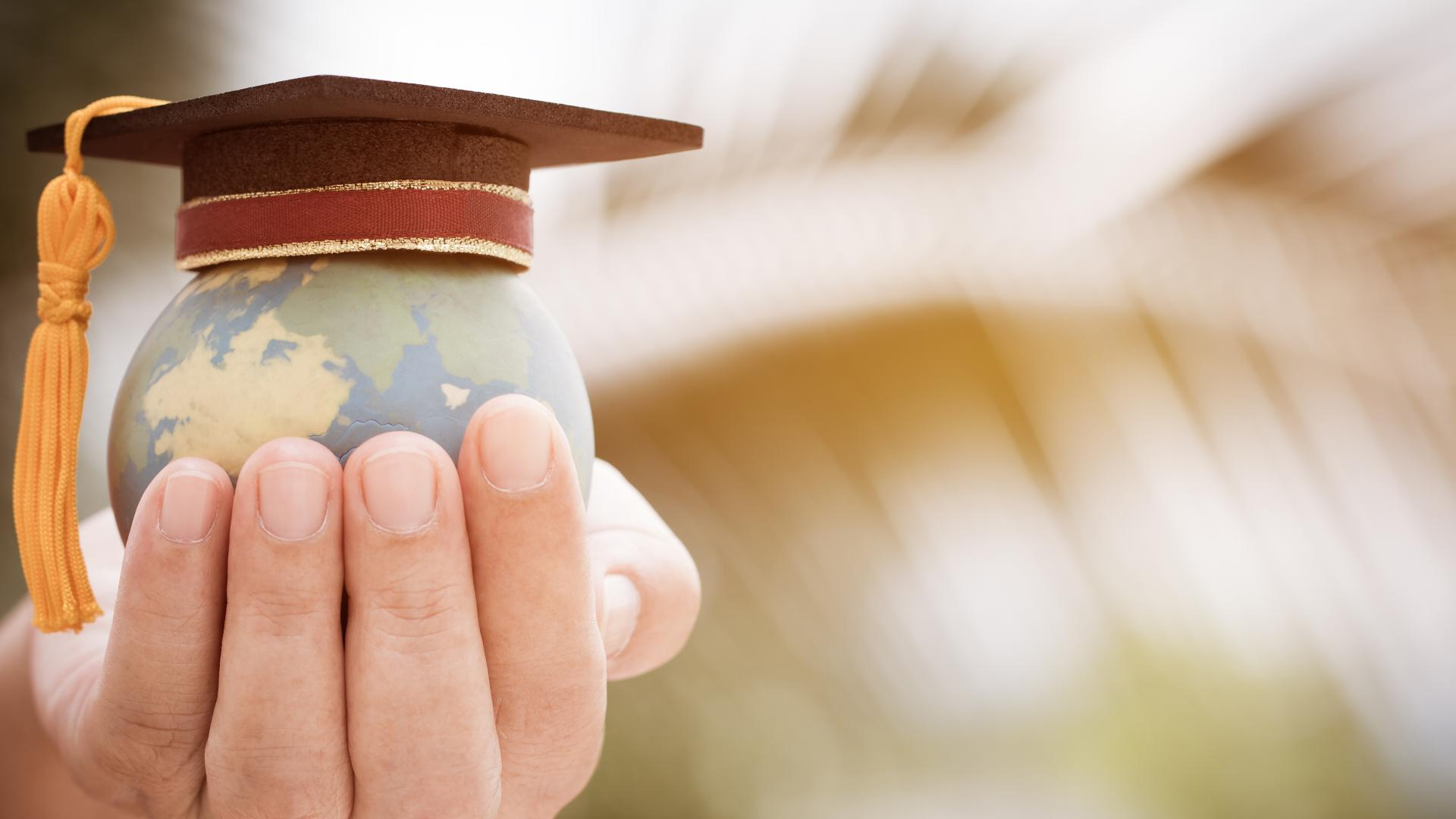 A person holding a mini globe in their hands with a graduation cap on top