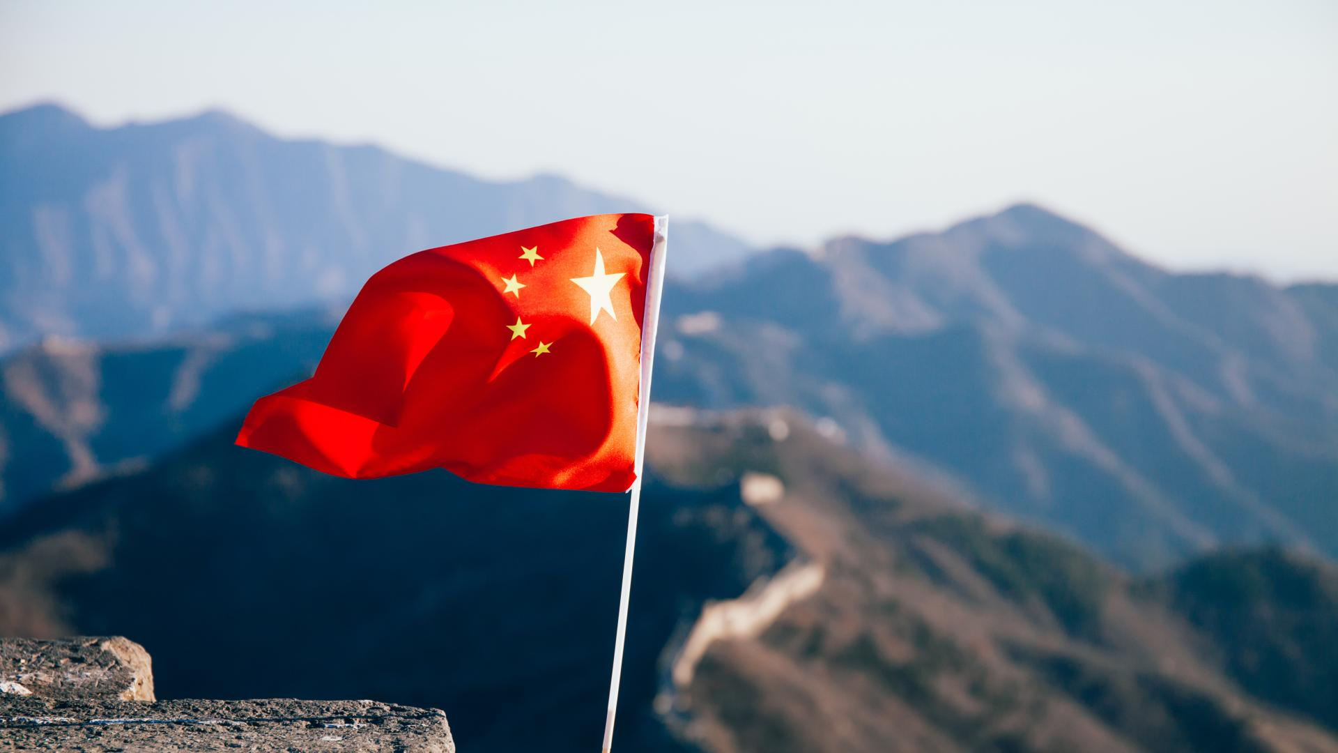 China flag flying over mountains in China