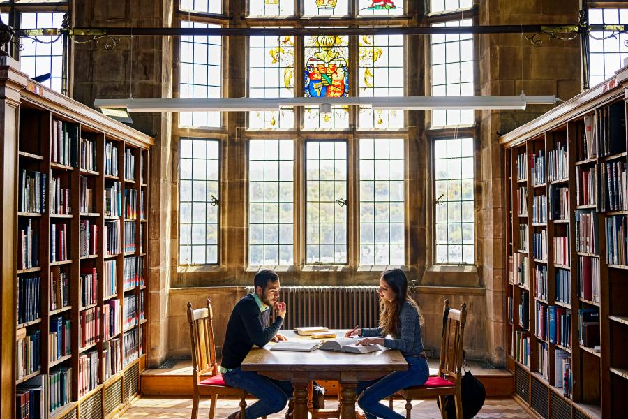 Students working at the Main Arts' Shankland Library with stained glass window in the background