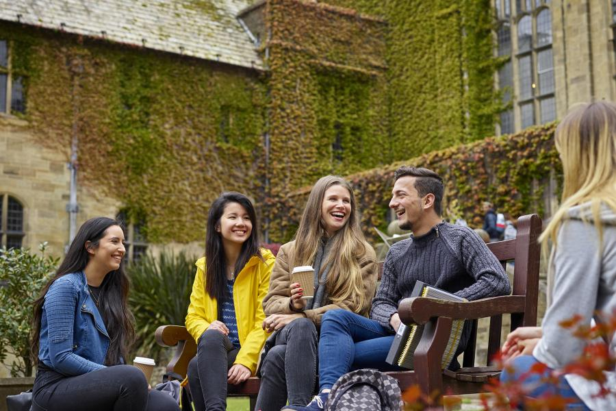 Students socialising on a bench in the inner quad of the University's Main Arts building