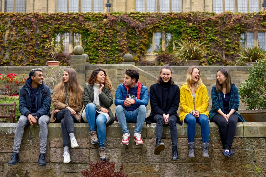 Students sitting on the wall in the inner quad of the Main Arts Building