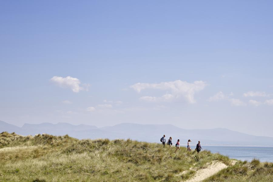 A group of students walking along the beach with the mountains in the background