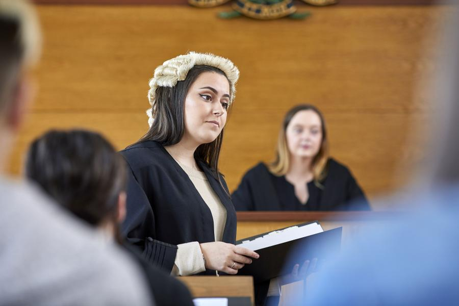 A student wearing a robe and wig in a moot court