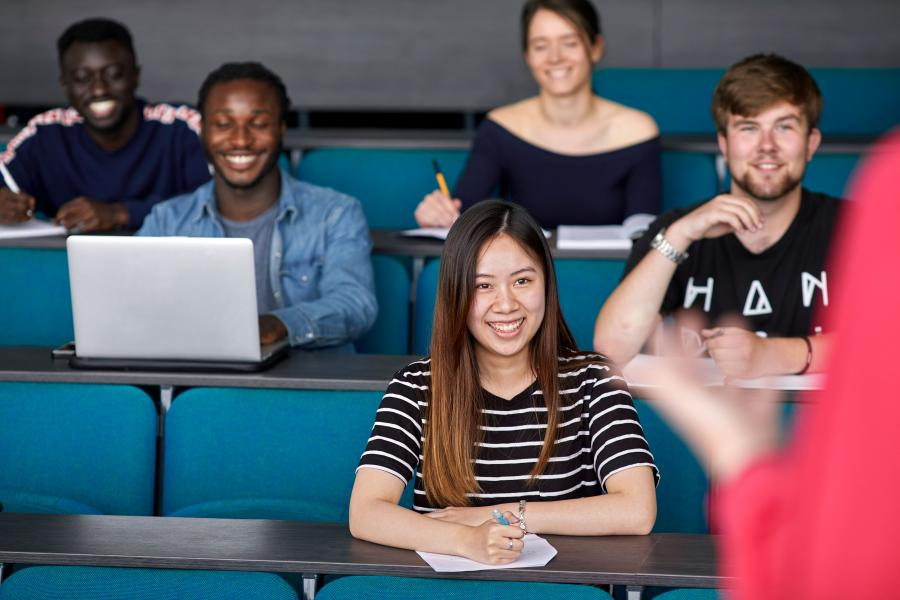 A group of students smiling during a lecture