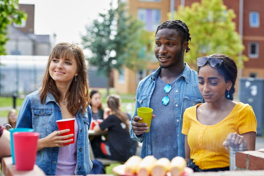Students socialising outside halls of residence at Ffriddoedd Student Village