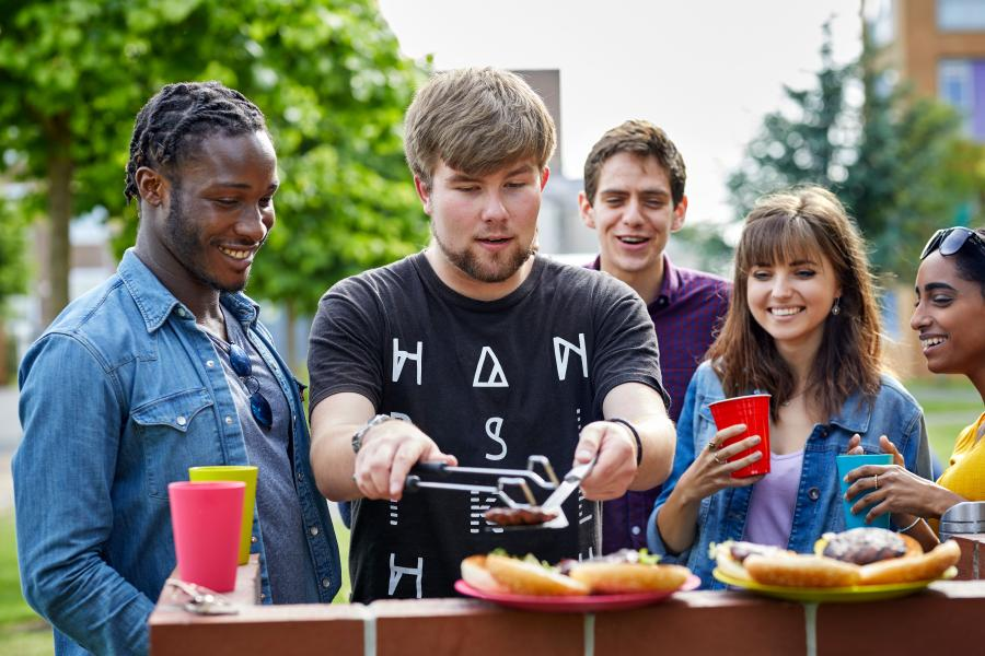 A group of students enjoying a BBQ outside halls of residence at the Ffriddoedd Student Village