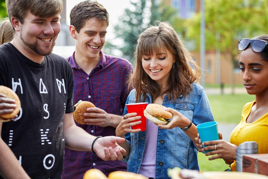 Students enjoying a BBQ outside halls of residence at the Ffriddoedd Student Village