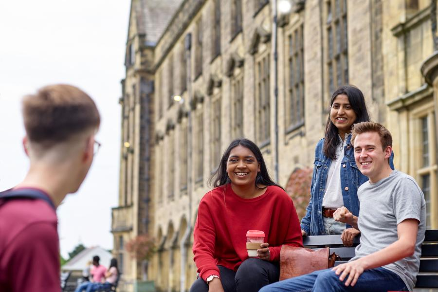 A group of students socialising on a bench on the terrace of the Main Arts building