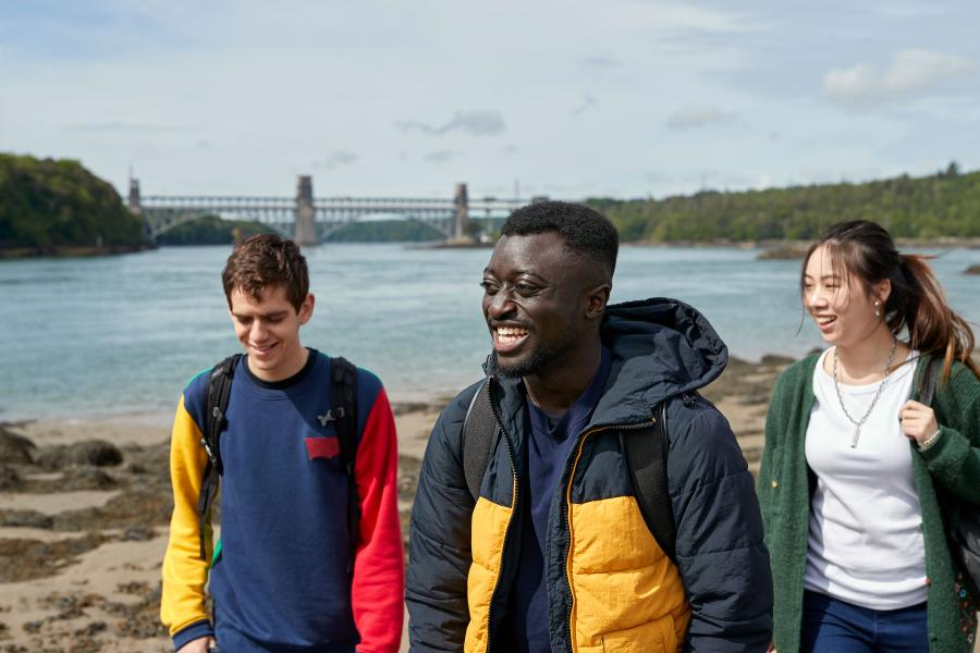 Students walking with the Britannia Bridge in the background