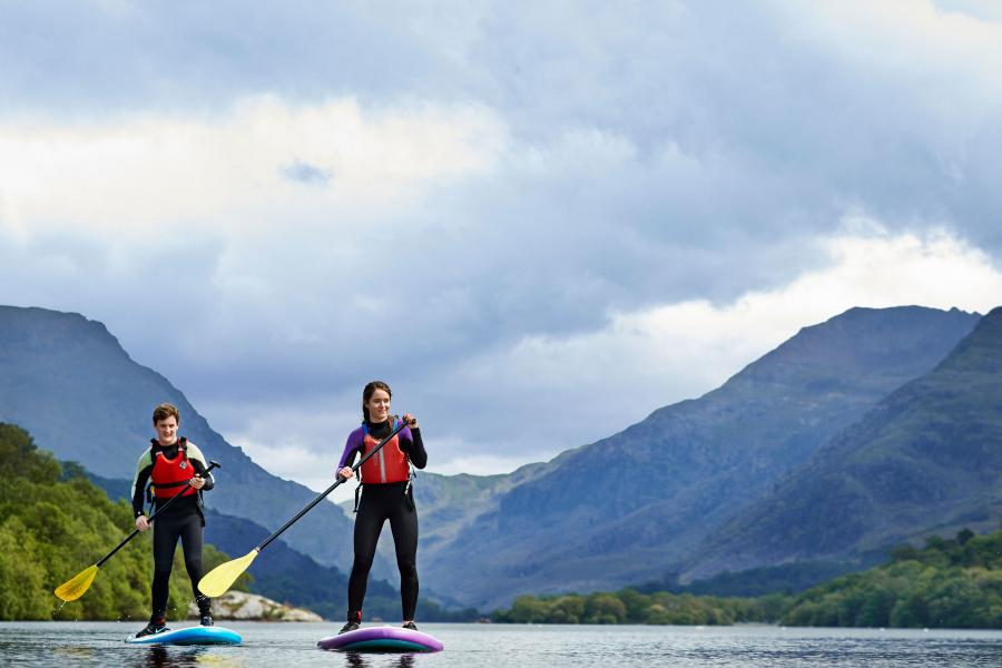 Two students paddle boarding on Llyn Padarn Lake in nearby LLanberis with the Snowdonia mountain range in the background