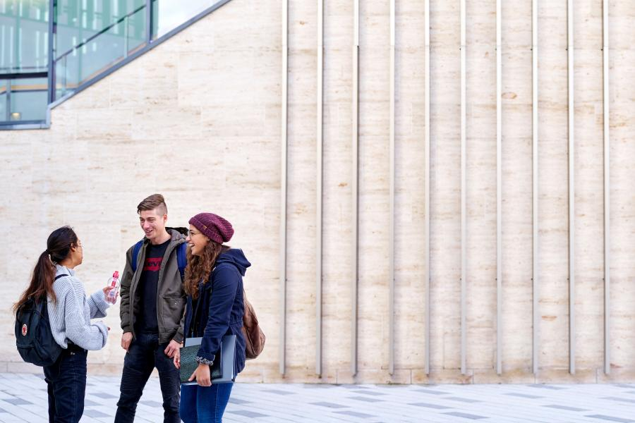 A group of students talking outside Pontio on their way to a lecture