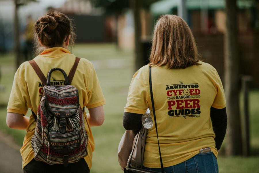 A couple of Peer Guides walking through Ffriddoedd Student Village during Welcome Week