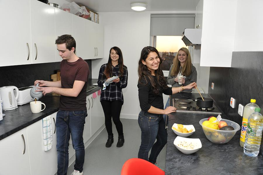 Students cooking in shared kitchen at halls of residence