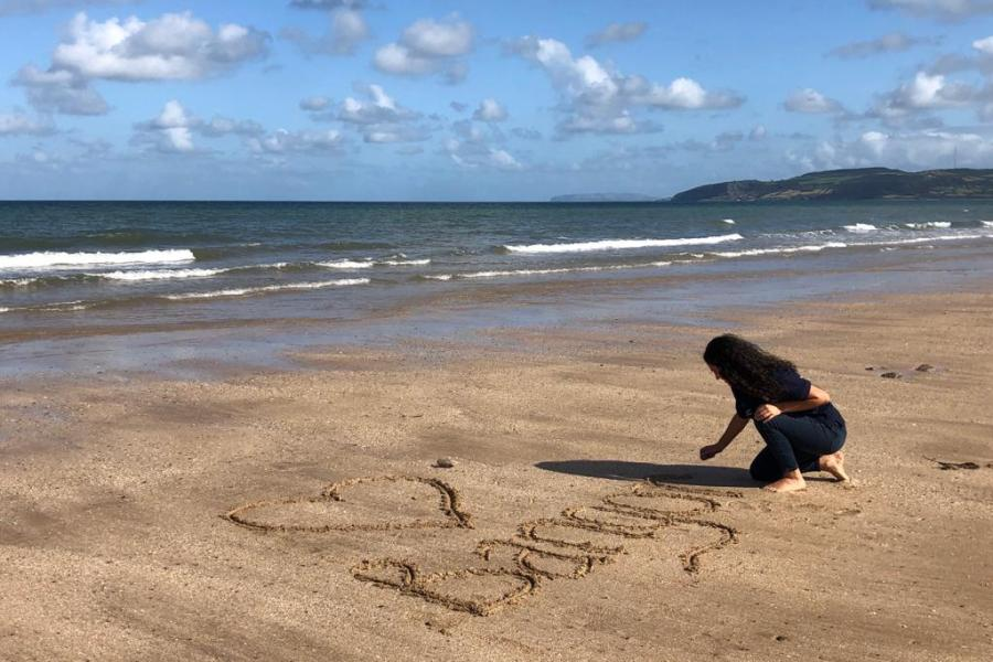 Student writing I Love Bangor in the sand on a beach during Welcome Week