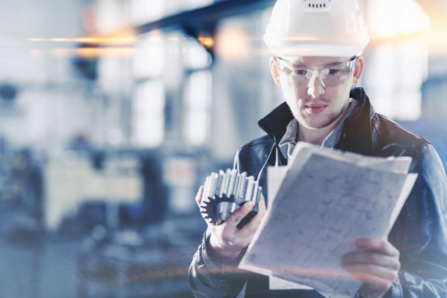 Engineer holding a engineering part and checking paper plans