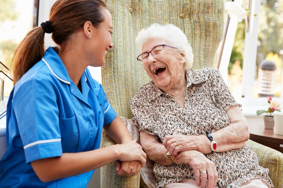 Woman sitting in a chair and talking to a nurse in a nursing home