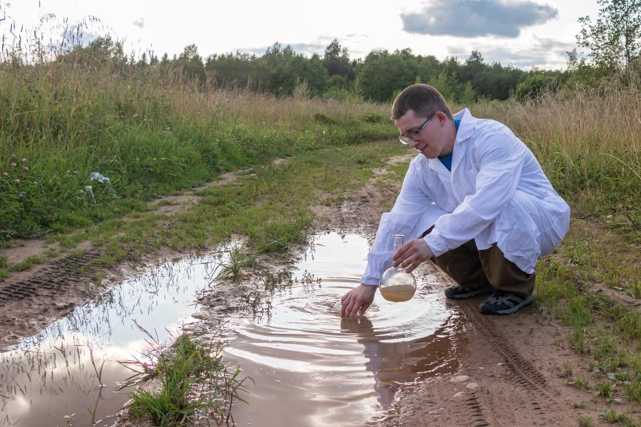 Laboratory assistant takes a water analysis in a puddle