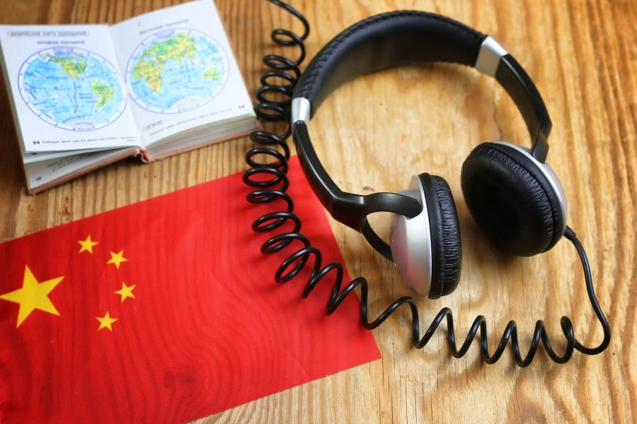 Table with headphones, book and Chinese flag