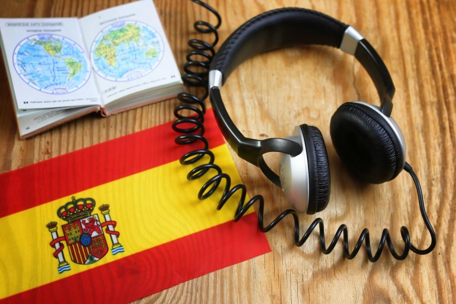 Headphones and book with a Spanish flag on a desk.