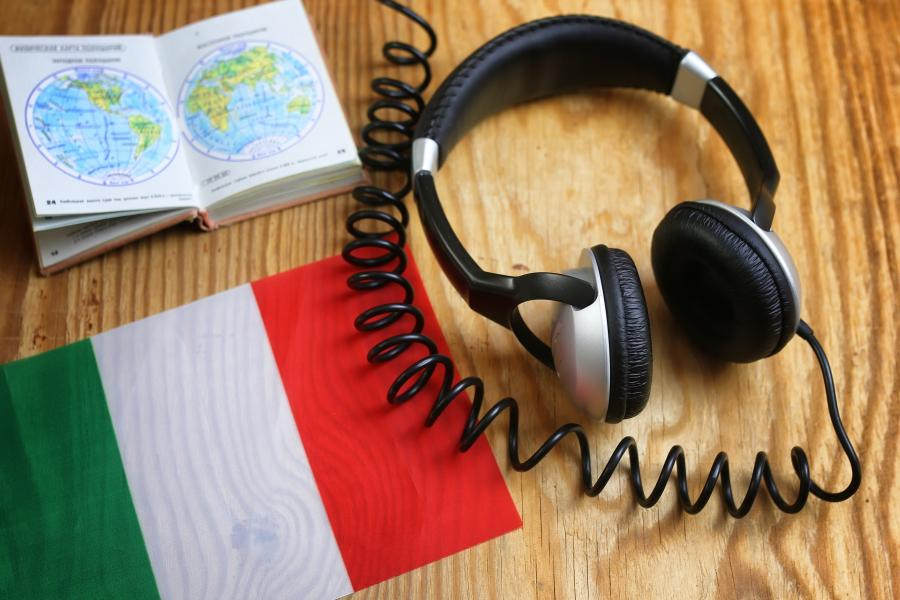Headphone and book on a desk with an Italian flag.