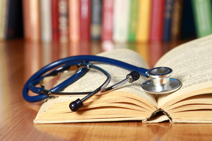 A stethoscope lying on an open book