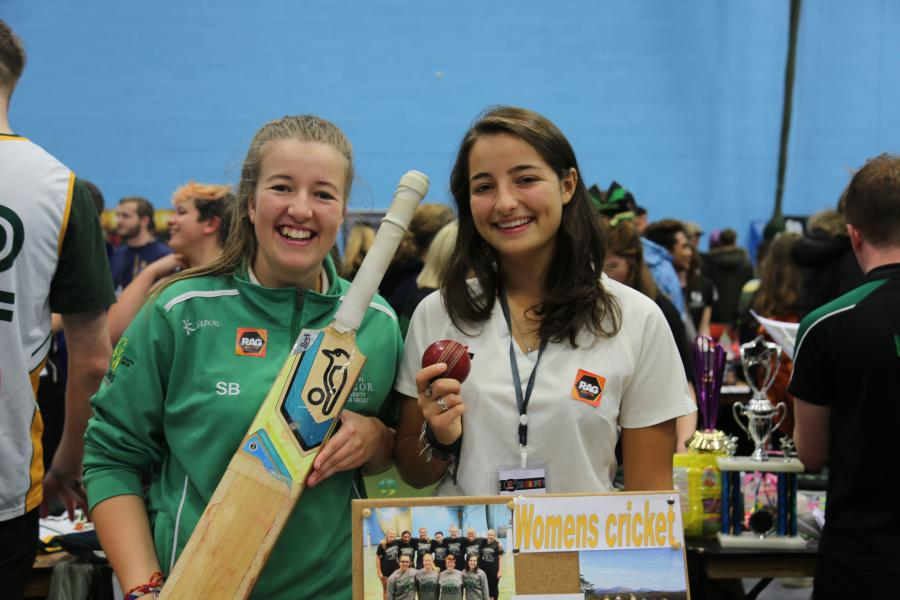 Two students from the Women's Cricket club at the Serendipity Fair during Welcome Week