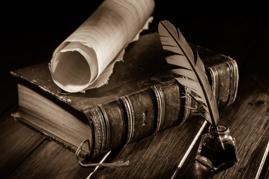 Image of a desk with a leather-bound book, scroll and quill.