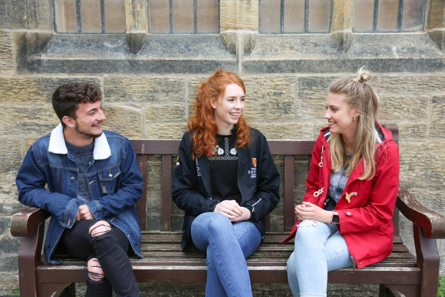 Three students sat on a bench on campus talking to each other