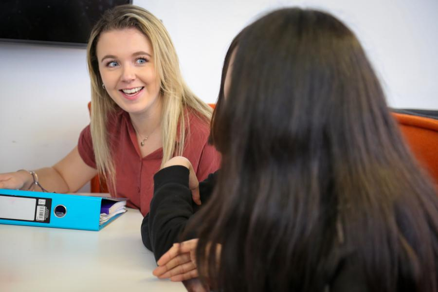 Two students working together in shared learning space, in Pontio