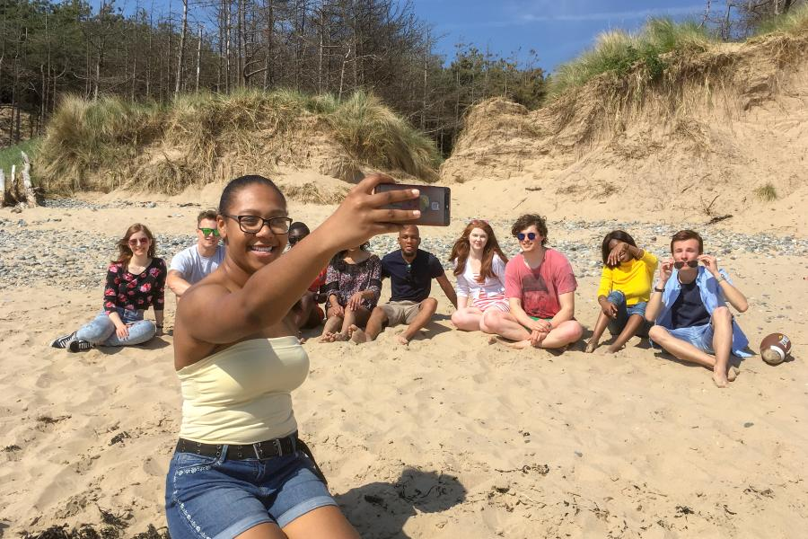 A group of students enjoying the sun, taking a selfie on the beach