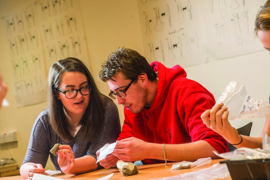 two archaeology students looking at artifacts in archaeology seminar